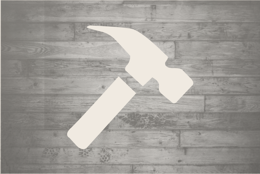 Outline of a white hammer against a wooden background